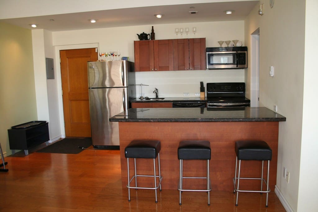 This is the kitchen, it has a sink, a microwave, and oven, with a stainless steel fridge complete with cutlery and cups.