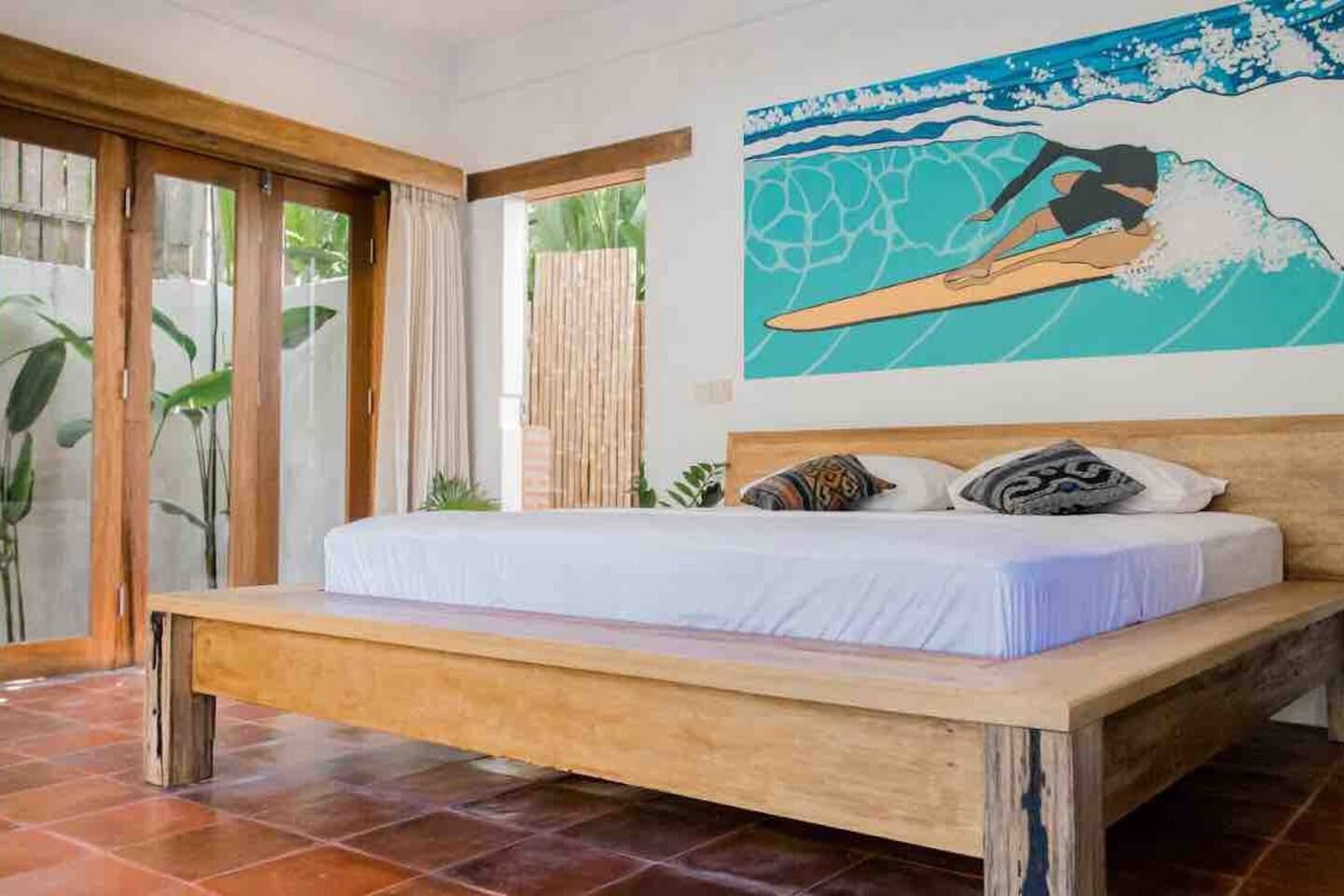 Grand floor bedroom featuring a garden view. The wall features a hand painted mural by a local artist. The room is fitted with AC, seating and desk, a comfy bed and clothes storage.