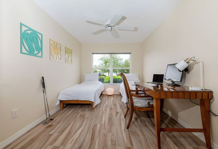 Third bedroom with two twin beds and workspace (no closet)