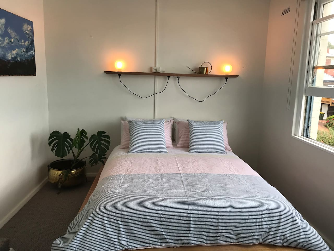 Bright main bedroom overlooks the backyard and the city