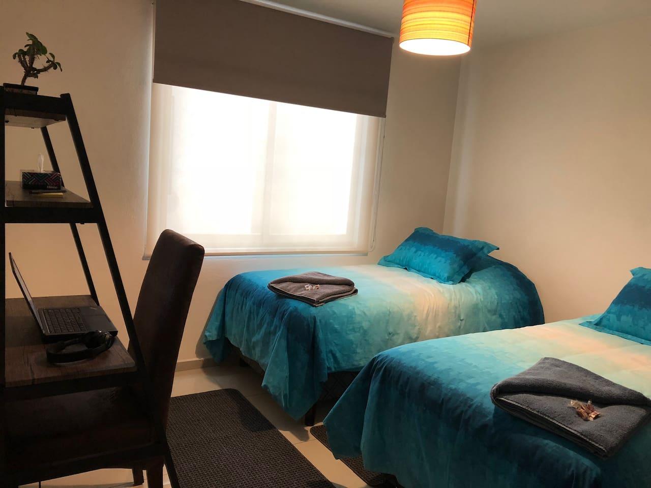 Dos camas individuales y escritorio para laptop