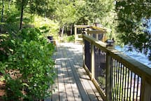 The sunny lakeside deck with stairs leading to a large dock - perfect for catching some rays.