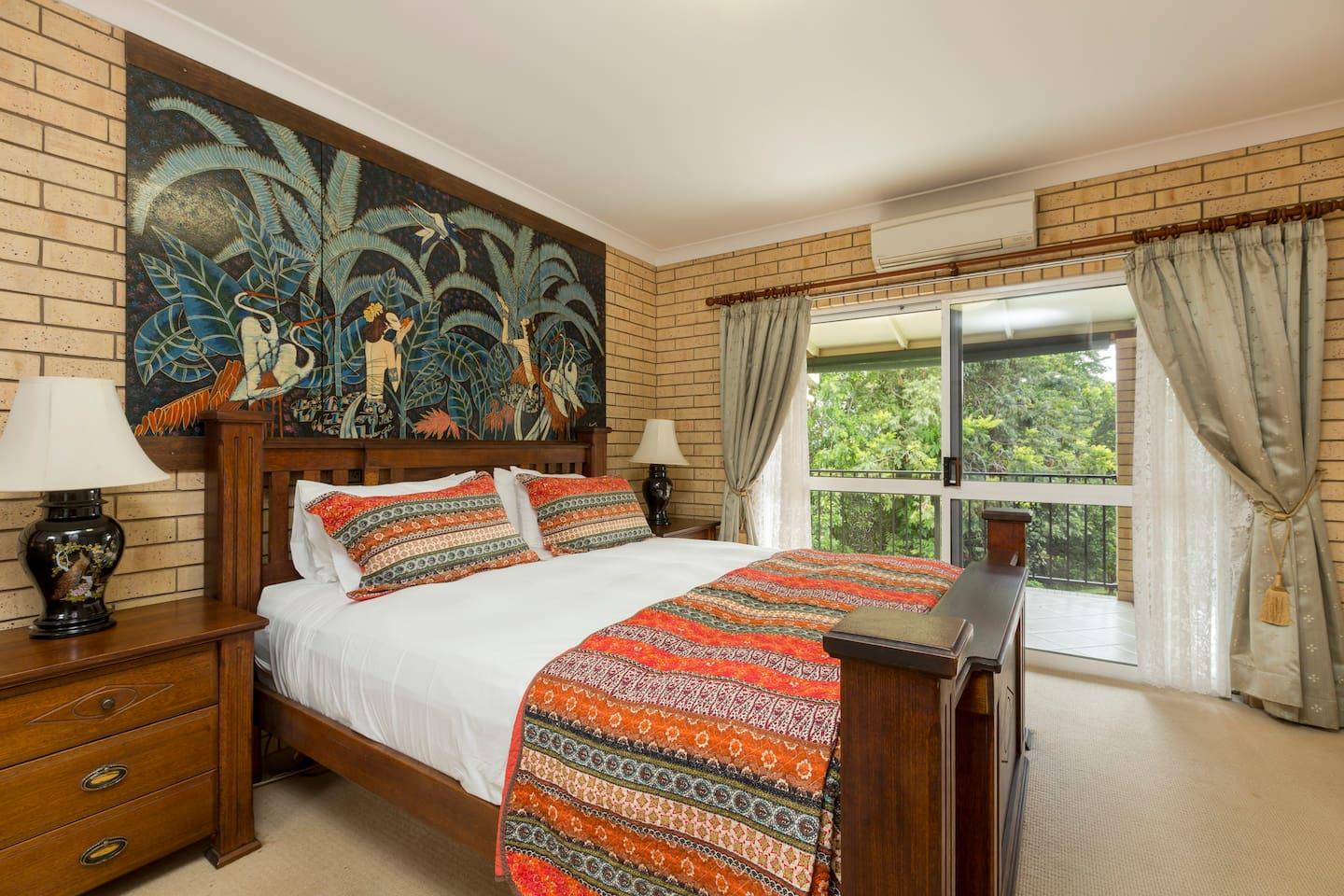 Main bedroom (main house) with a comfy king bed with a hidden surprise!   Sliding glass doors open to the veranda with a rainforest outlook.