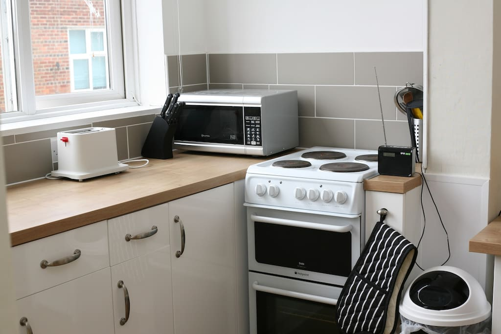 The kitchen has a fridge, coffeemaker, microwave, toaster and electric cooker with a oven and grill.