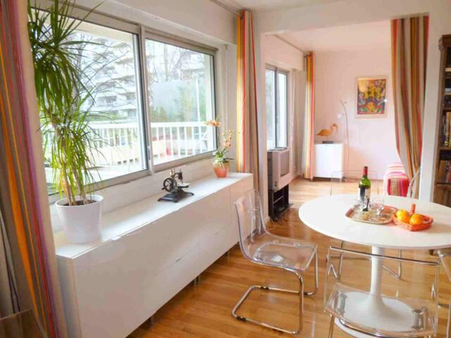 La salle de séjour ouverte sur la chambre, vue sur la terrasse, son salon de jardin et le parc.