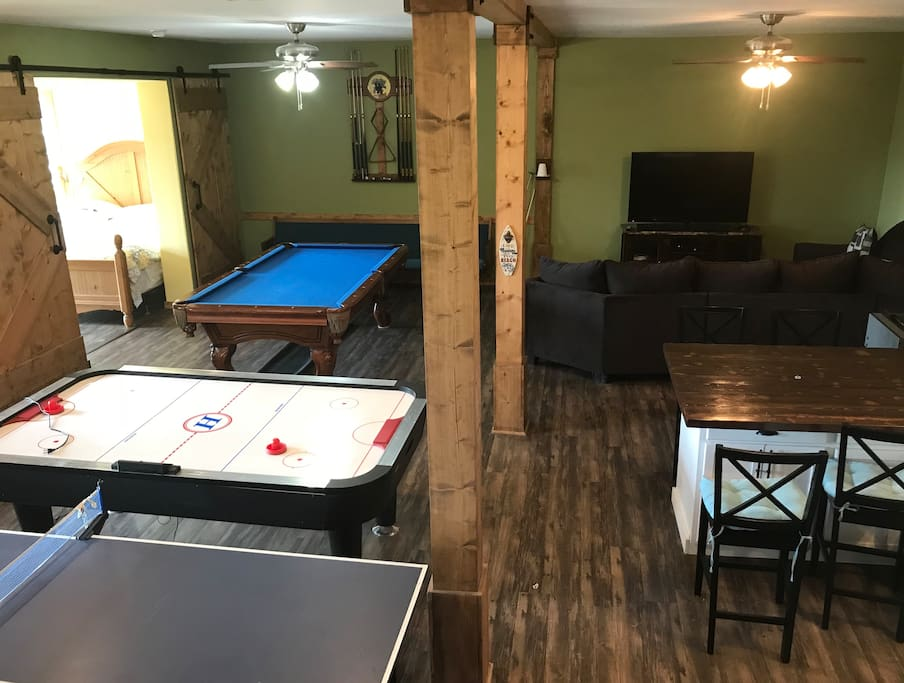 Living area includes tv, sectional couch, full size pool table, ping pong, air hockey, fooseball, darts and board games, full kitchen