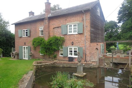 A converted watermill surrounded by farm land.