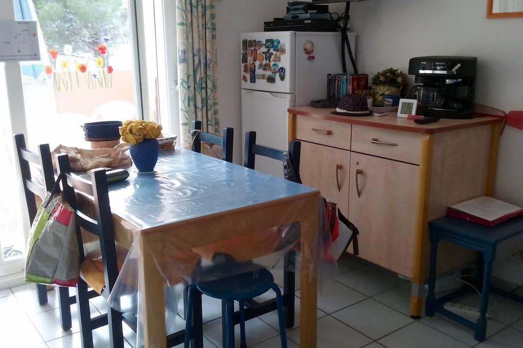 Salon avec table, meubles et électroménagers