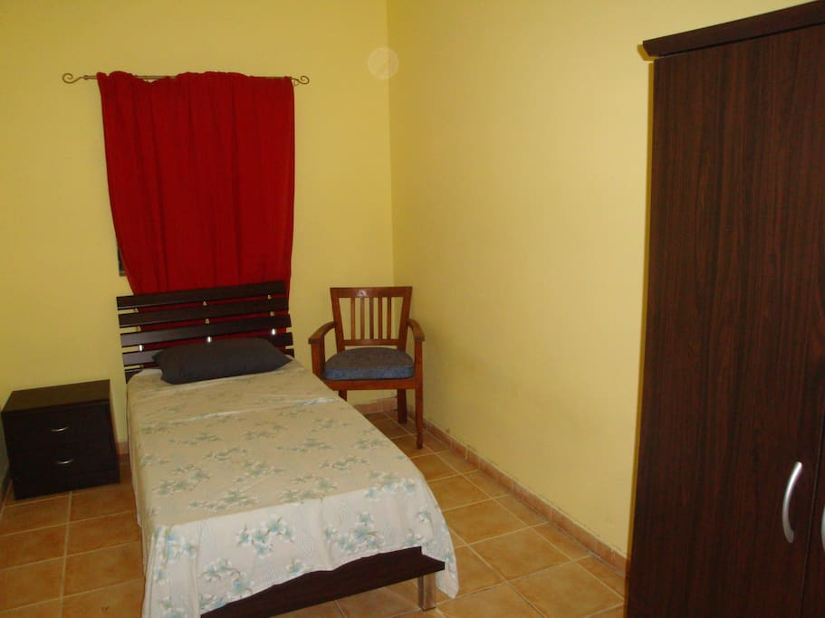 The bedroom also includes a wardrobe and a small cabinet, as can be seen in the photo