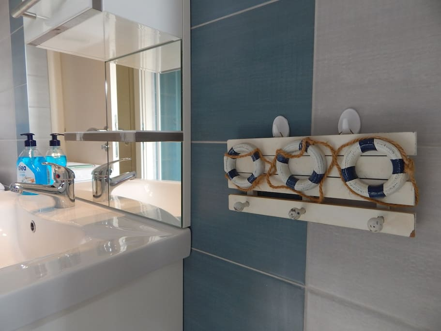 Bathroom with washing machine and towels provided