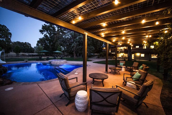 Wisteria-covered, lighted patio with seating by pool