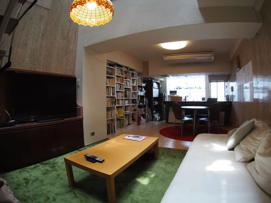 Living room equipped with large TV, sofa, chairs, and dining table, shared with 8 other residents