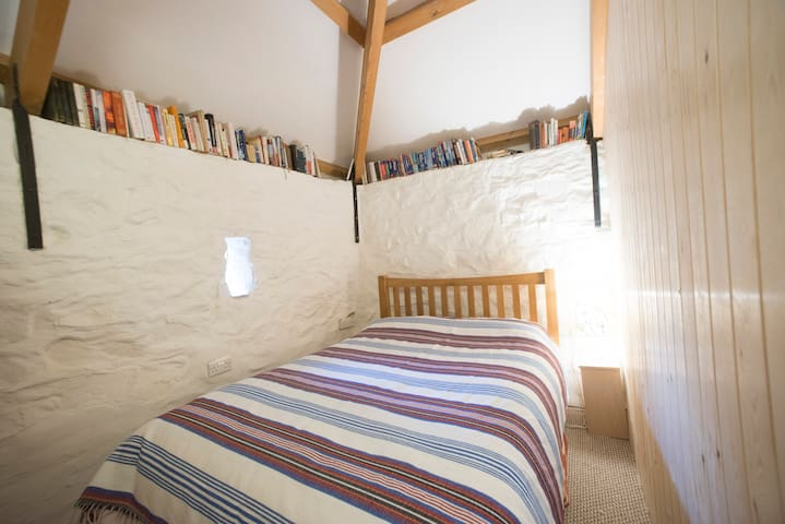 The cosy bedroom area of this open plan accommodation is right next to the bathroom and can be screened off as required.  The oak bed is a standard double bed without foot bars and is very comfortable.