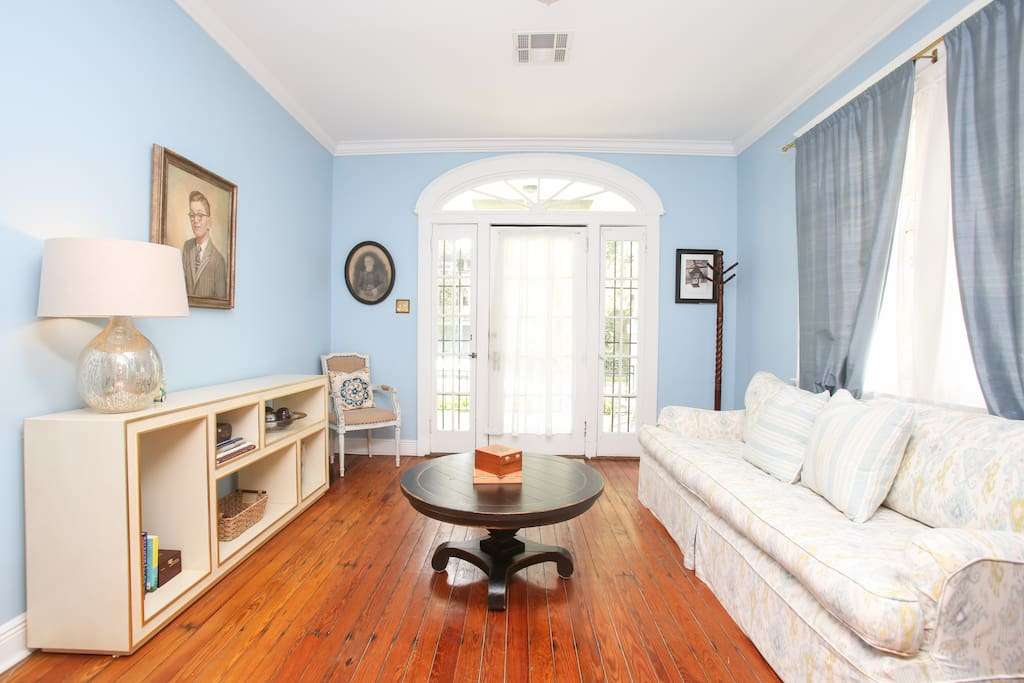 Welcome to the living room! Original cypress floors, comfy sofa.