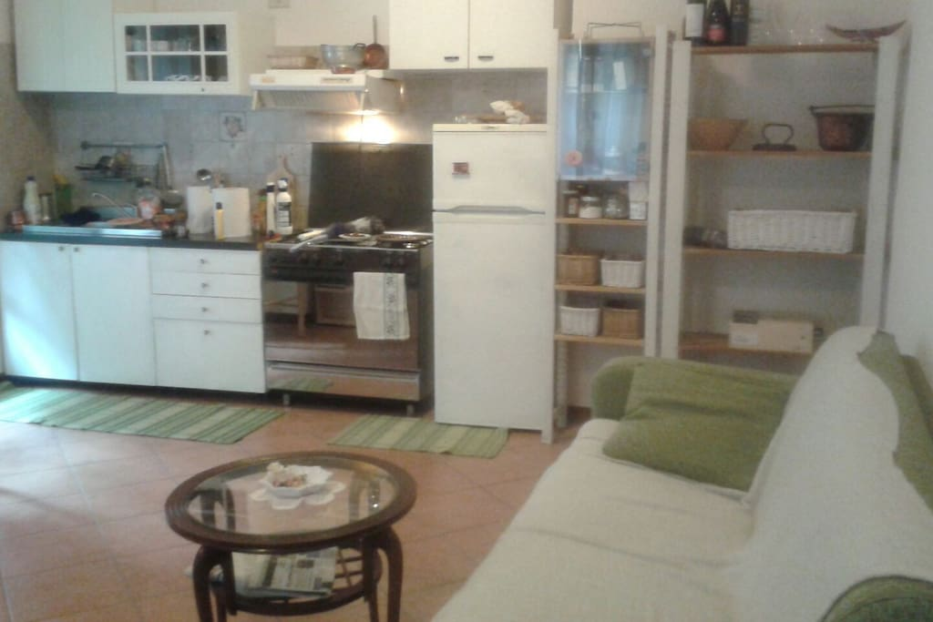 furnished kitchen with oven, fridge, microwave, kettle, toaster