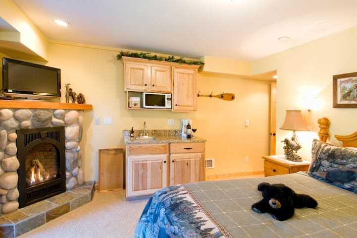 The Black Bear suite with queen sized bed, river rock gas fireplace and kitchenette fully stocked with dishes, wine glasses, silverware, waffle iron, coffee pot, microwave, fridge and breakfast in your room.