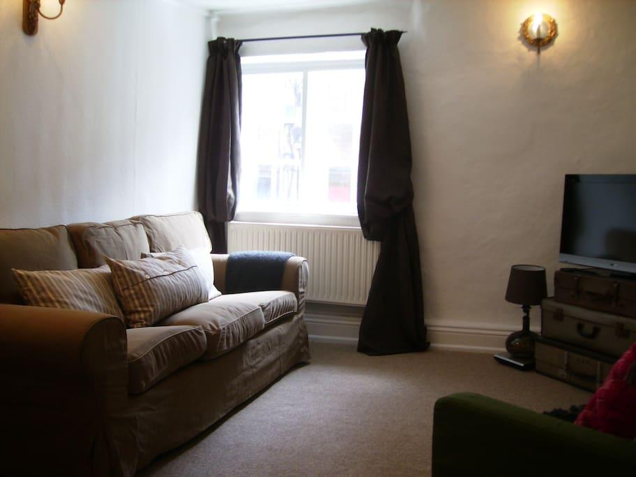 The living room is lovingly decorated with a selection of antiques, second hand items and new furniture.