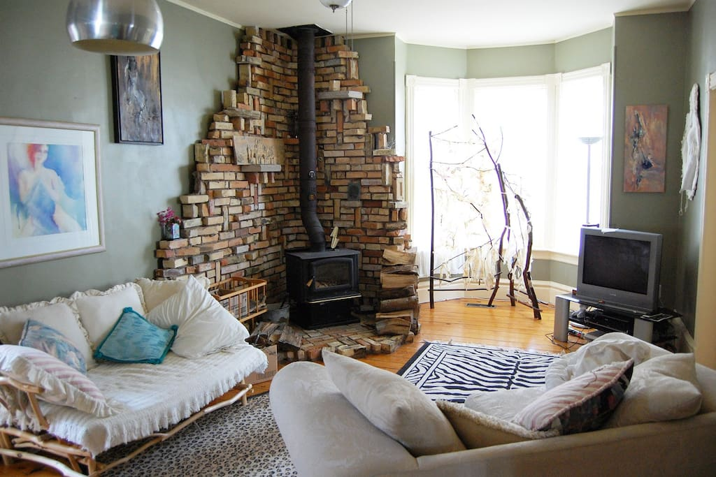 Living room with working wood stove and lots of art on the walls.