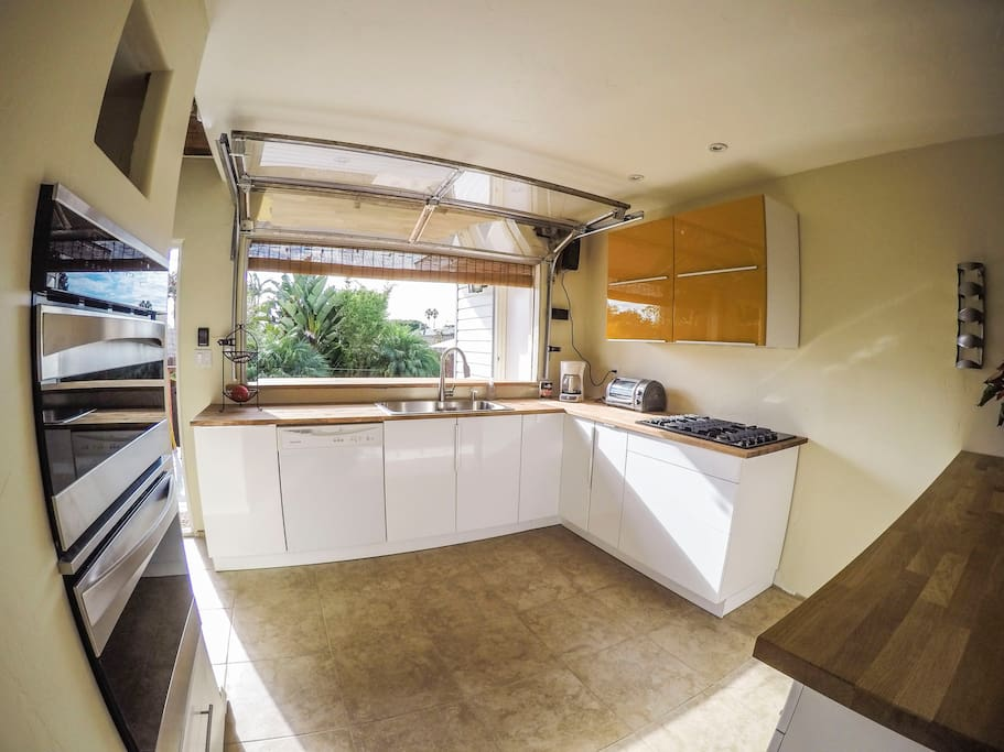 Custom roll-up kitchen window opens the space up for an indoor/outdoor gathering
