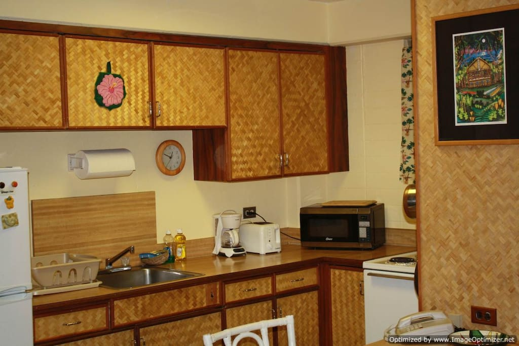 Kitchen, including microwave, stove, refrigerator cabinets with dishes and towels.