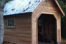 Covered shed can be used for projects, chopping wood, or even camping outside.