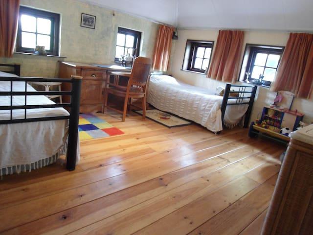 Tweede slaapkamer op de begane grond met 2 bedden en wastafel