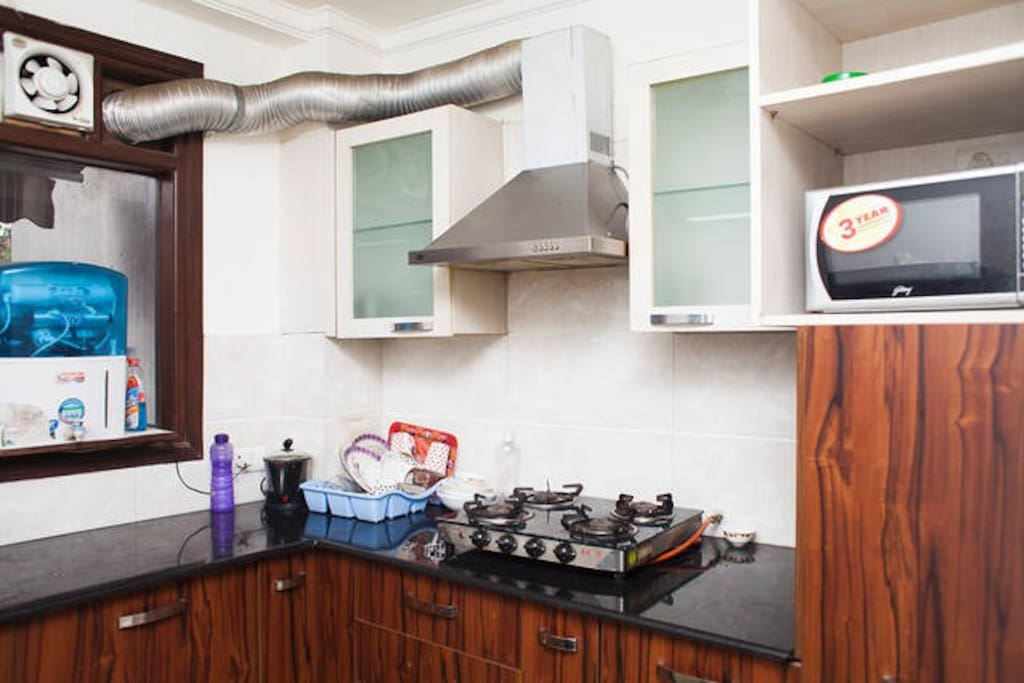 Fully equipped Modular Kitchen with Stovetop, Refrigerator, Microwave, cookware, etc.