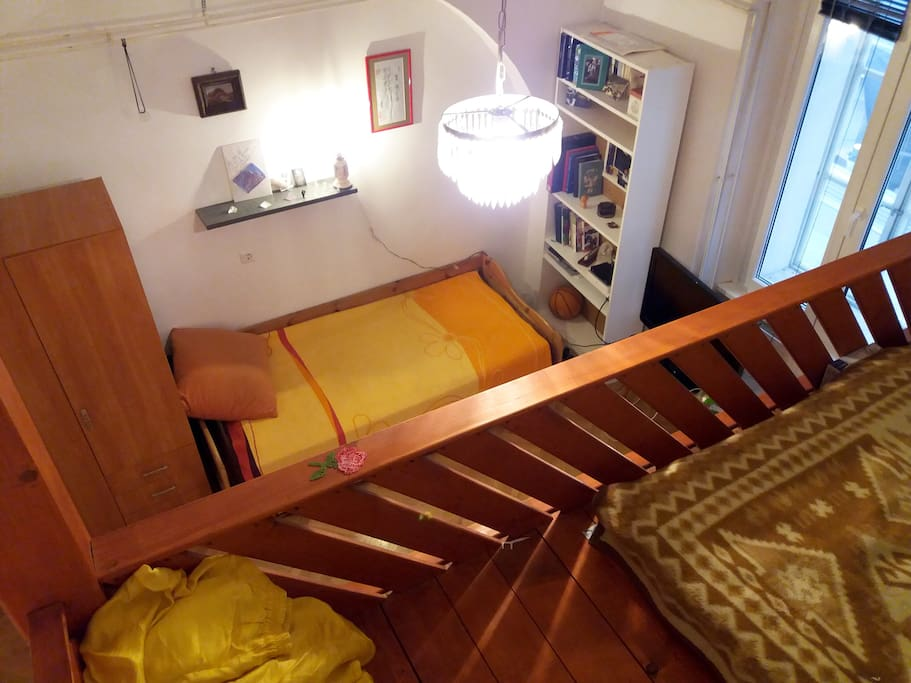 A view from upper bed. The ceilings are 3.5 meters high and there is a normal standing height on the upper double bed.