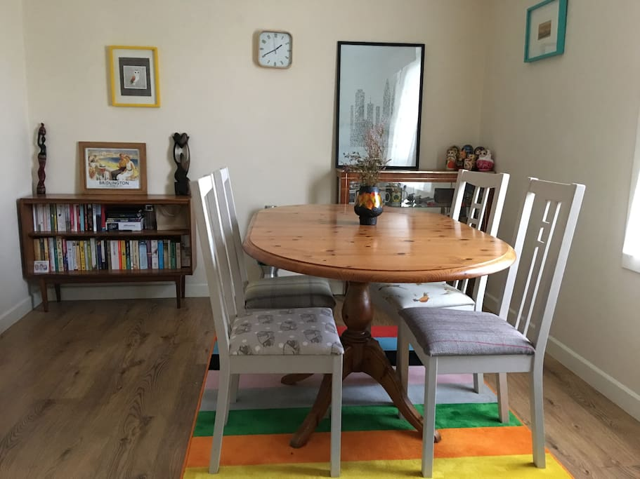 Communal dining room with an eclectic mix of furniture, including bespoke upholstered and hand painted chairs.