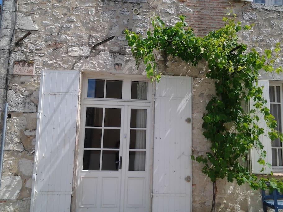 Grape vines cascade over the door.