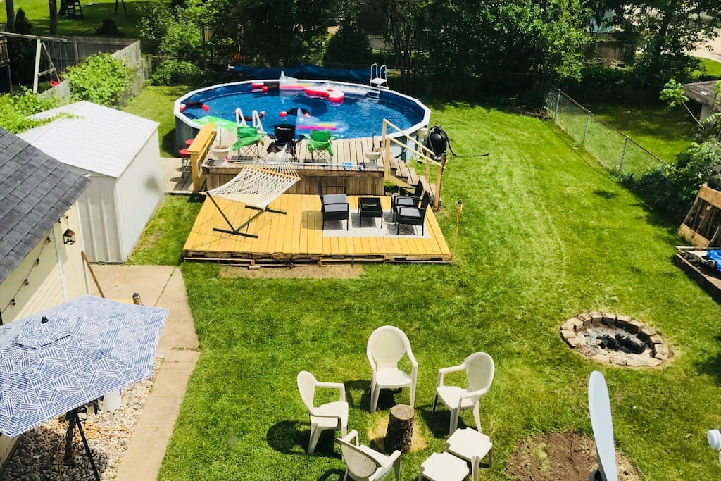 Fenced in backyard with pool,deck,bar/grill,fire pit, and hammock