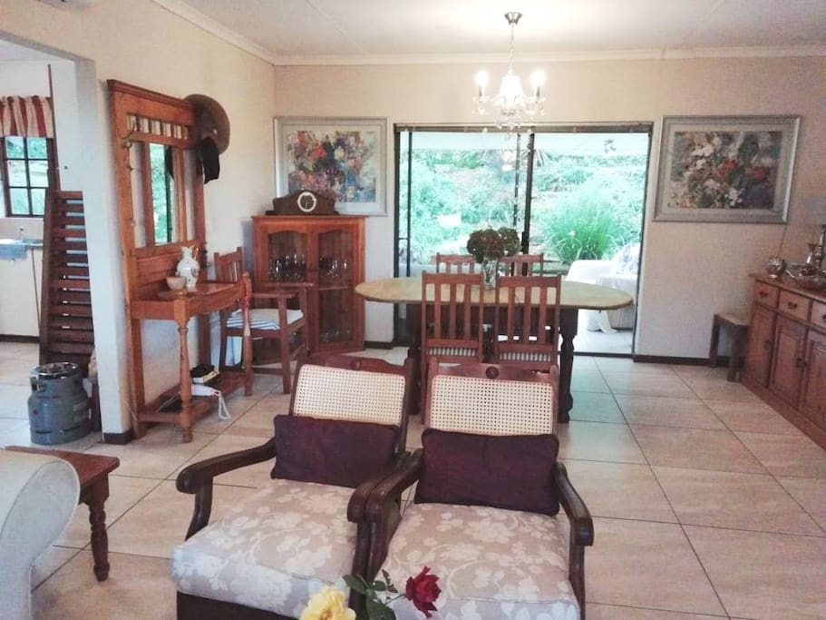 Open plan lounge dining. Leads to covered verandah with added seating. TV in lounge with sofa and loose chairs. Tiled floor.