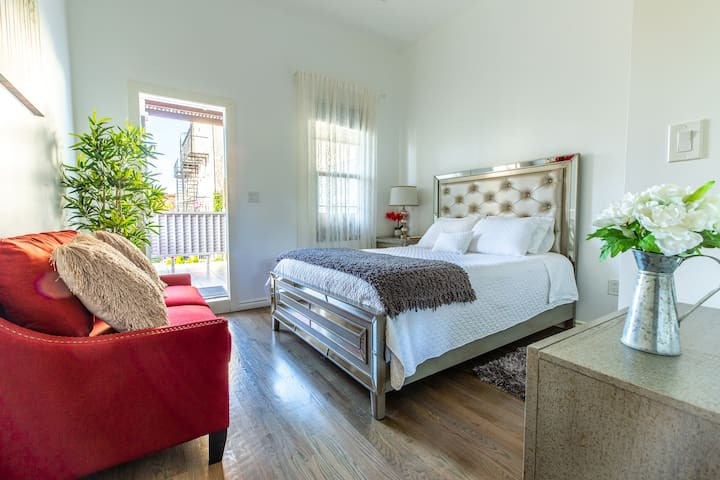 (Master Bedroom) Queen Size Bed with Private Backyard Balcony. Bedroom has a Wireless & USB Phone Charger and a Digital Safe Box. Small Sofa and Reading Lamp.