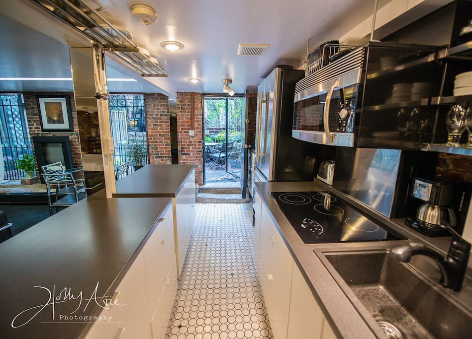 Three large windows overlook the walk out patio..  8 feet of island on your left, 14 feet of kitchen on your right -- there are more than 20 drawers in the base cabinets and open shelving on the WHITE SUBWAY TILED walls on your right.