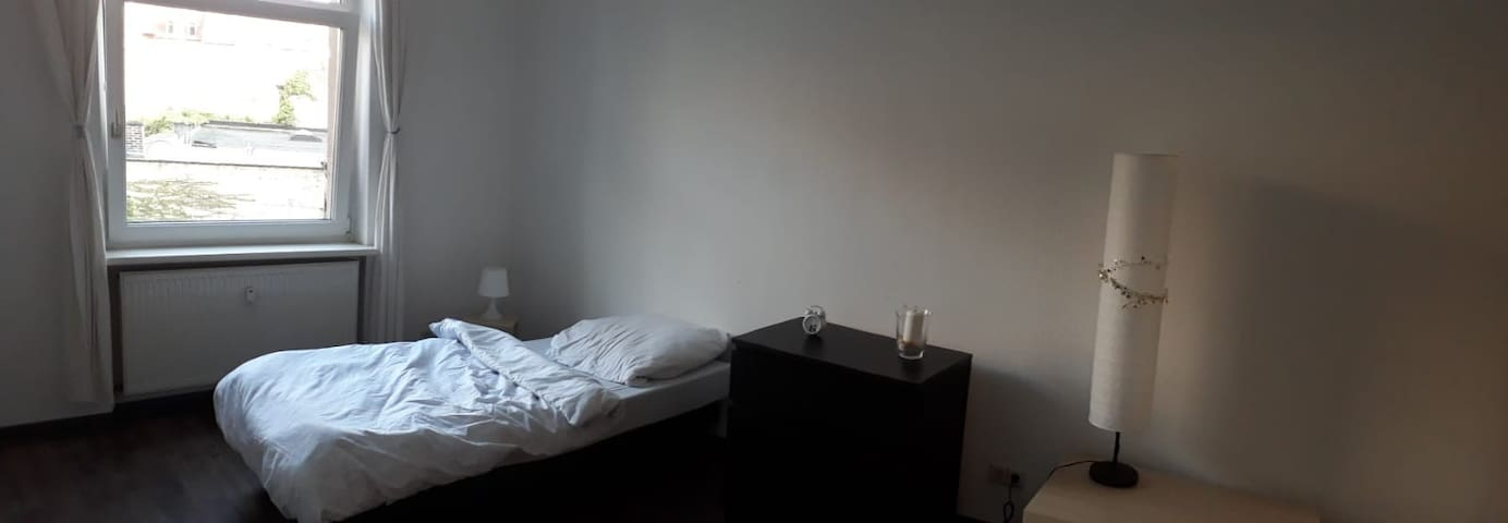 Room with a single bed, a working desk and chair, and drawers