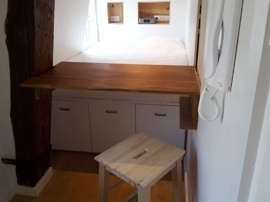 A table pops out of the wall and seats two very comfortably, one sitting on the bed, the other on the stool.