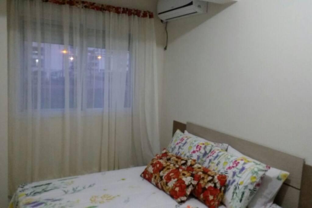 quarto social de casal com ar condicionado.