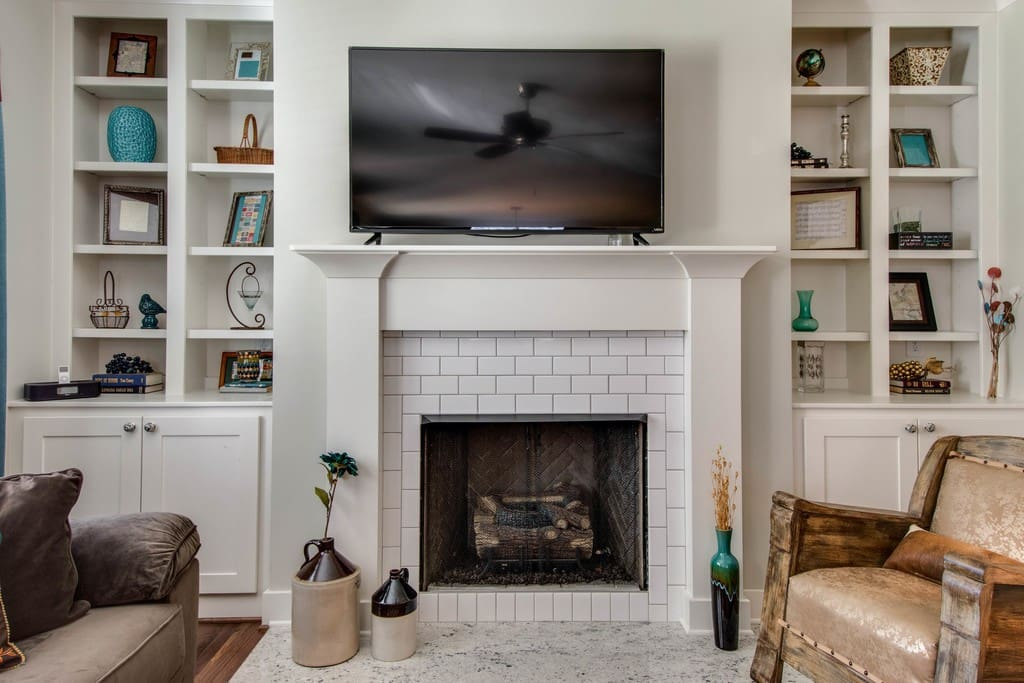 Decorative fireplace and flat-screen TV in the living area.