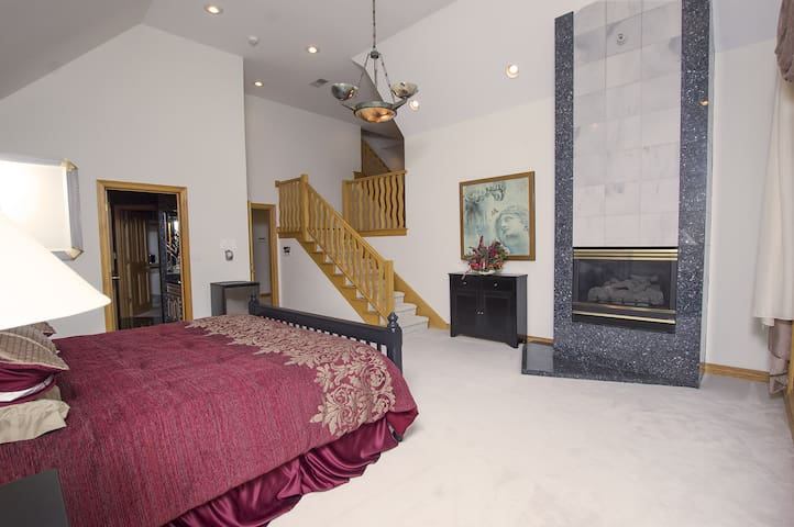 Bedroom with king bed, gas fireplace, and adjoining two rooms if needed  with five single beds. Second level living room area. Private bathroom with a large jetted tub. This room is great for couples, families or if you just have extra guests!