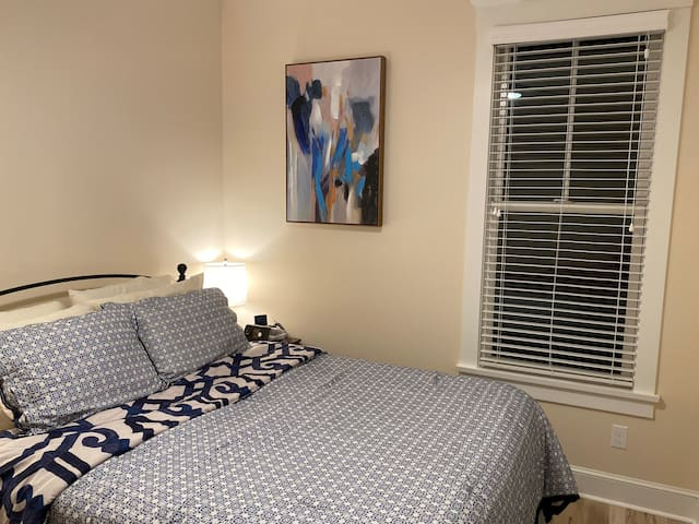 Guest bedroom with a queen size Sleep Number bed, 2 nightstands, table lamps, dresser, ceiling fan, and deep closet.