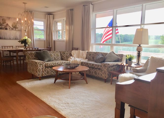 Relaxing Mid-Century Modern Family Farmhouse Living Room. Large Living Room features 1950's style blond brick Fireplace, large Smart TV, original wood floors, huge picture window and Piano.  Panoramic views of farm and pastureland.