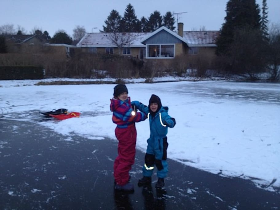 The kids in winter on the frozen lake behind our house with the house in the background