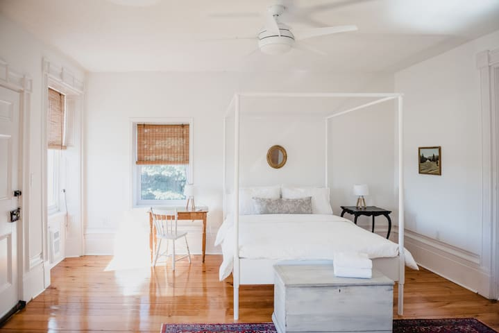 The main floor queen bedroom is the largest in the house and includes three windows and a ceiling fan for the perfect cross breeze. The little antique desk has a view of the side yard and enough room for a laptop.