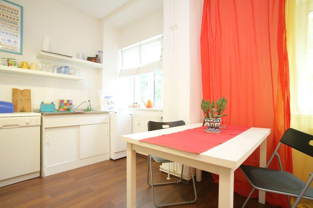 Küche mit Geschirrspüler, Waschmaschine, Herd, Spüle, Mikrowelle, Tisch und Stühlen.