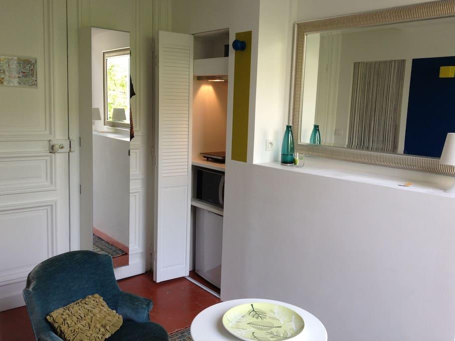 L'espace jour avec kitchenette et placard de rangement avec miroir