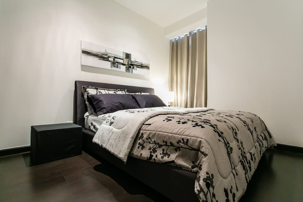 Queen size bed with comforter, reading lamp and Air-conditioned