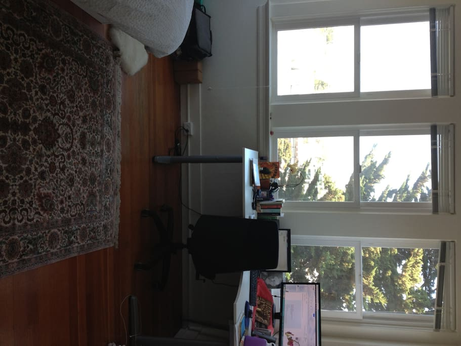 The room is 1/2 windows with a spectacular view, wood floors, and a large desk are shown here.