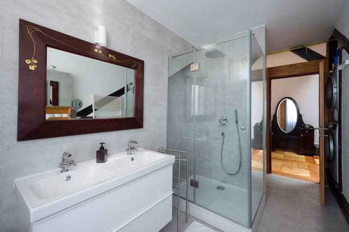 The bathroom is modern and new with a classic mirror for a contrast