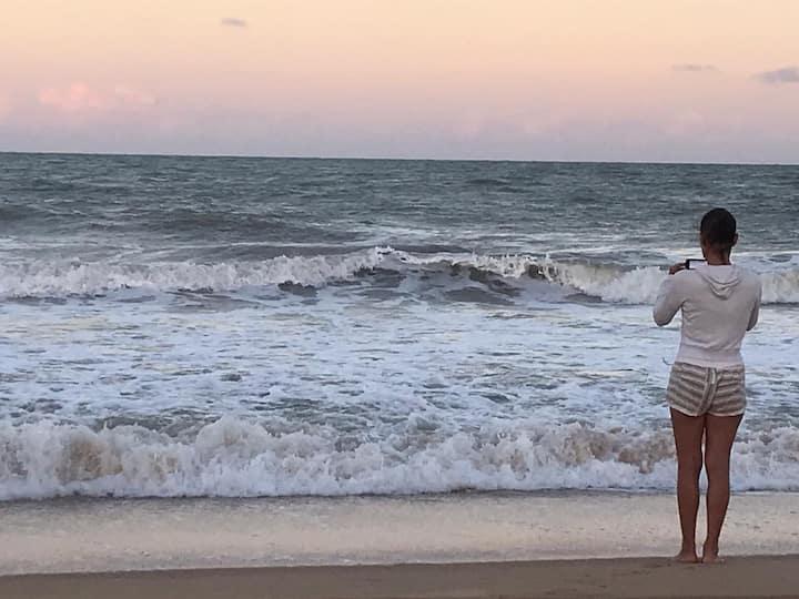 Pé na areia à luz do sol e da lua.