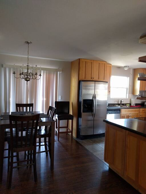 Kitchen has glasstop electric range, microwave, dishwasher, and refrigerator, garage disposal, pull out trash in cabinet, sliding glass door to deck area